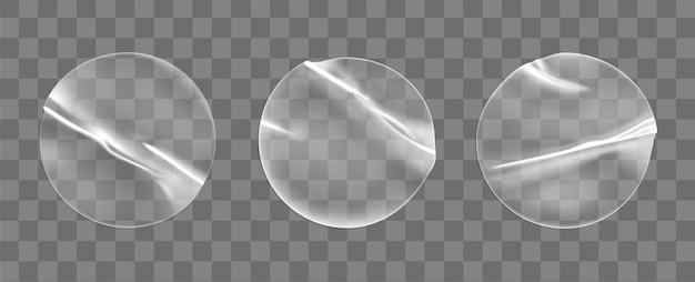 투명한 원형 접착 스티커는 투명한 배경에 격리된 세트를 조롱합니다. 접착 효과가 있는 플라스틱 구겨진 둥근 스티커 라벨. 레이블 또는 가격표 템플릿입니다. 3d 현실적인 벡터 프로토 타입