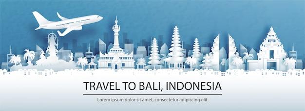 バリ島デンパサールへの旅行を伴う旅行広告。街のスカイラインのパノラマビューと紙で世界の有名なランドマークのインドネシアのコンセプトカットスタイルのイラスト。
