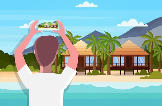 Путешествия блоггер с помощью смартфона камеры, принимая фото или видео тропического пляжа с бунгало в прямом эфире потокового летнего отдыха концепция морской пейзаж фон горизонтальный вид сзади портрет