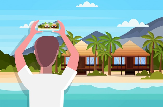 Travel blogger using smartphone camera taking photo or video of tropical beach with bungalows blogging live streaming summer vacation concept seascape background horizontal rear view portrait