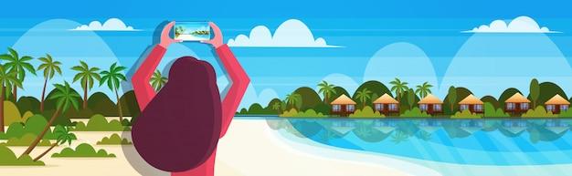 열 대 바다 해변 사진 또는 비디오 블로깅 라이브 스트리밍 여름 휴가 개념 바다 배경 가로 세로에 스마트 폰 카메라 여자를 사용하여 여행 블로거
