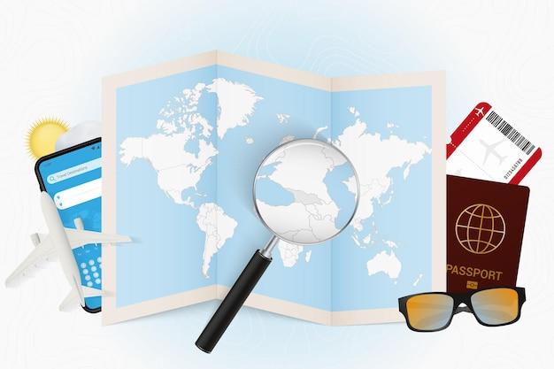 여행 목적지 조지아, 여행 장비가 있는 관광 모형, 조지아에 돋보기가 있는 세계 지도.