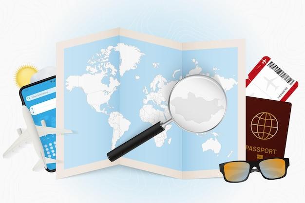 Место назначения монголия, туристический макет с туристическим оборудованием и карта мира с увеличительным стеклом на монголии.