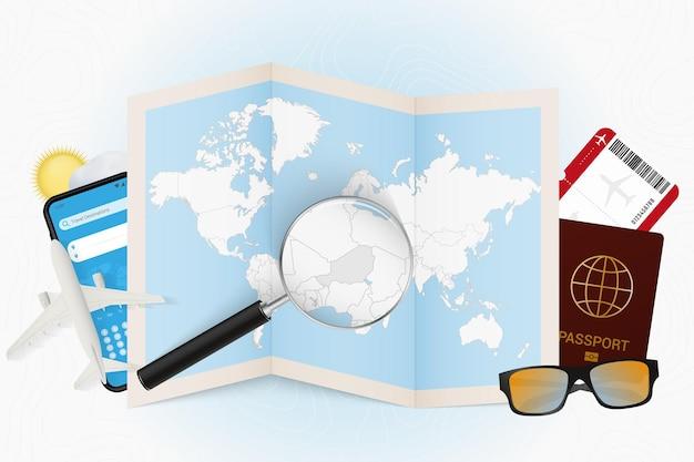 Пункт назначения нигер, туристический макет с туристическим оборудованием и карта мира с увеличительным стеклом на нигере.