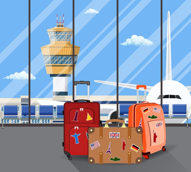Travel suitcases inside of airport with a plane