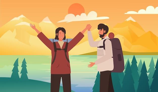 ハイキングポイントに立っているカップルの幸せな観光客と一緒に夏の目的地を旅行する