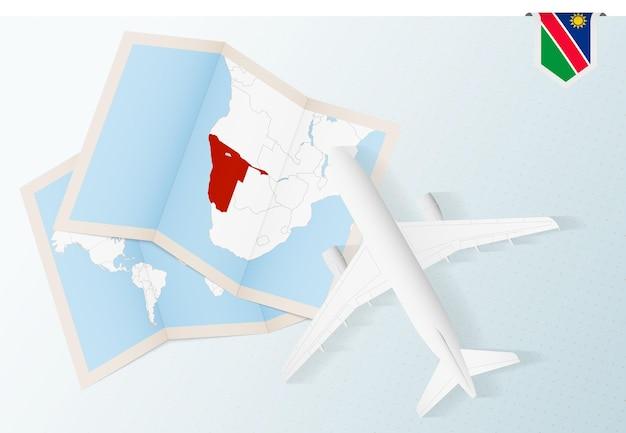 Путешествие в намибию, вид сверху на самолет с картой и флагом намибии.