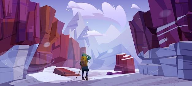 冬の山での旅行者、旅行の旅、冒険。バックパックと木のスタッフを持つ観光客は、高い山頂を見ている岩だらけの雪景色に立っています。