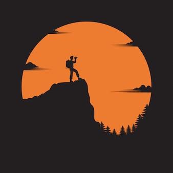 Путешественник с рюкзаком стоит, глядя на долину