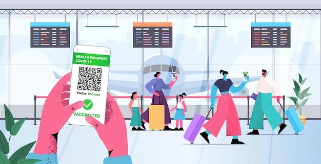 스마트폰 화면에서 디지털 면역 여권을 사용하는 여행자는 위험이 없는 covid-19 pcr 인증서 코로나바이러스 면역 개념 공항 터미널 내부 전체 길이 수평 벡터 일러스트레이션
