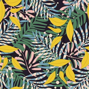 Trending abstract seamless pattern with colorful tropical leaves and plants on black background