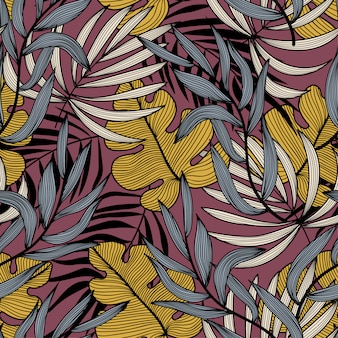 Trending abstract seamless pattern with colorful tropical leaves and plants on pink background