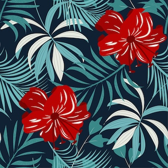 Trending bright seamless pattern with colorful tropical leaves and flowers on dark