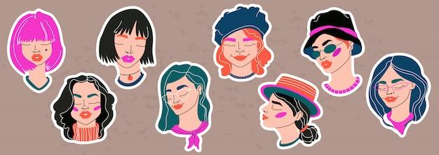 Модные молодые девушки сталкиваются наклейки. коллекция рисованной девочек-подростков. модные цветные цифровые рисунки. изолированные элементы на светло-коричневом фоне. милые женские лица для веб и печати.