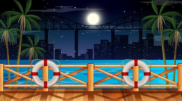 Scena di paesaggio spiaggia tropicale di notte con il paesaggio urbano