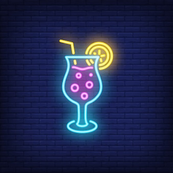 Tropical cocktail neon sign. fizzy alcohol drink with straw on dark brick wall background
