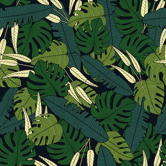 Tropical leaves vector seamless pattern on black background.