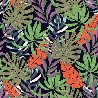 明るいオレンジと緑の葉を持つ熱帯のシームレスなファッションパターン