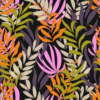 明るいオレンジとピンクの葉と花を持つ熱帯のシームレスパターン