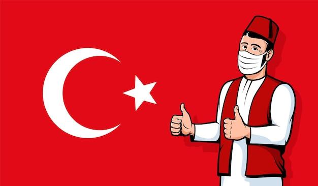 トルコの旗の背景に医療マスクのトルコ人男性ポジティブトルコ親指アップジェスチャー