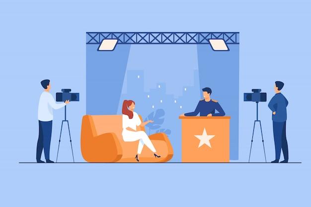Телеведущий берет интервью у знаменитости в студии
