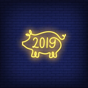 Twenty nineteen neon sign with yellow pig shape. Night bright advertisement.