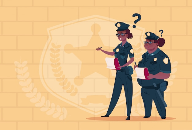 Two african american police women holding boxes with office staff fired wearing uniform female guards on blue bricks background
