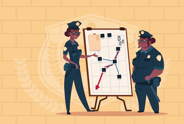 Two african american police women planning action on white board wearing uniform female guards on blue bricks background