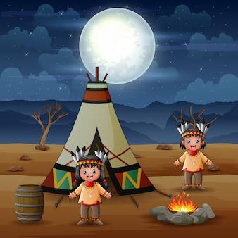 Мультфильм двух американских индейцев с вигвамами в племенной локации Premium векторы