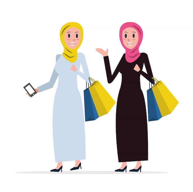 Two arab women coming out of shopping with bags