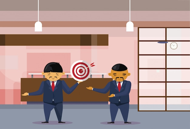 Two asian business men holding target with arrow in center