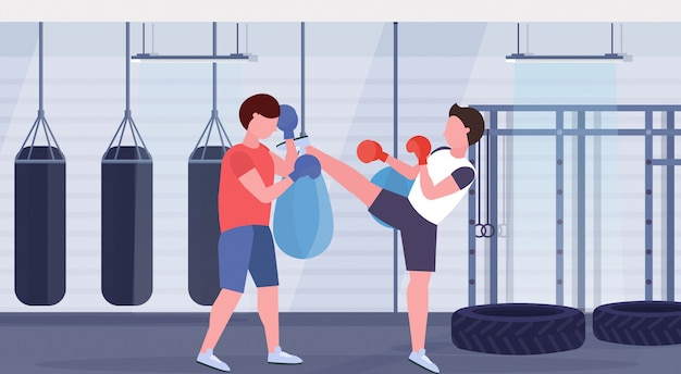 Two boxers training kick boxing exercises fighters in gloves practicing together modern fight club with punching bags healthy lifestyle concept flat horizontal full length