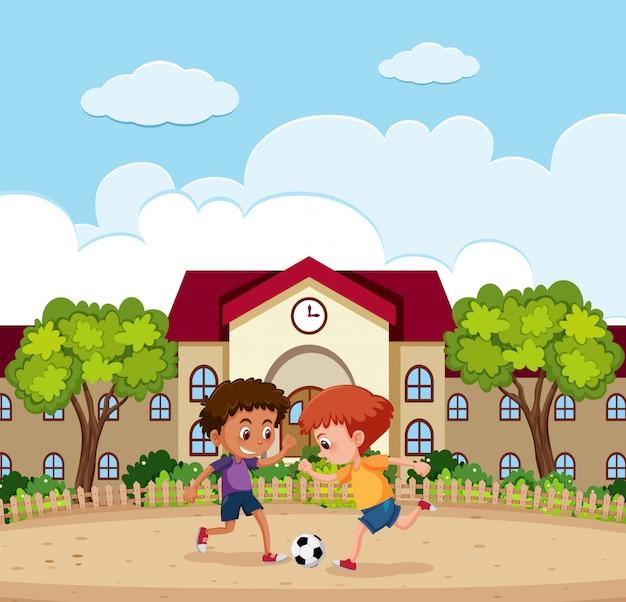 Два мальчика играют в футбол за пределами школы