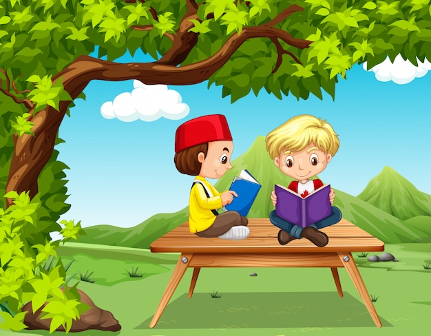 Two boys reading books in the park