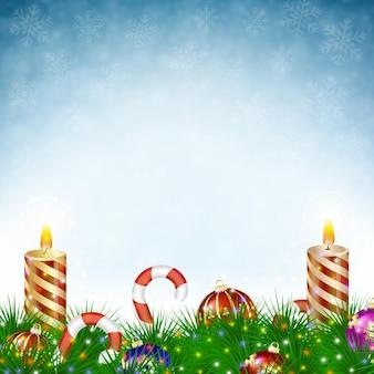 Две горящие рождественские свечи с елочными шарами, леденцами и сосновыми ветками в снегопаде на синем фоне