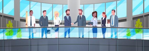 Два деловых человека, пожимающие друг другу руки в современном офисе, деловая встреча команды, успешное соглашение или