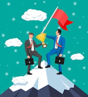 깃발과 트로피를 들고 산 꼭대기에 서 있는 두 사업가. 승리, 성공적인 임무, 목표 및 성취의 상징. 시험 및 테스트. 승리, 비즈니스 성공. 평면 벡터 일러스트 레이 션