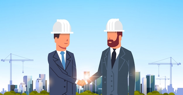 Two businessmen handshaking over city construction site