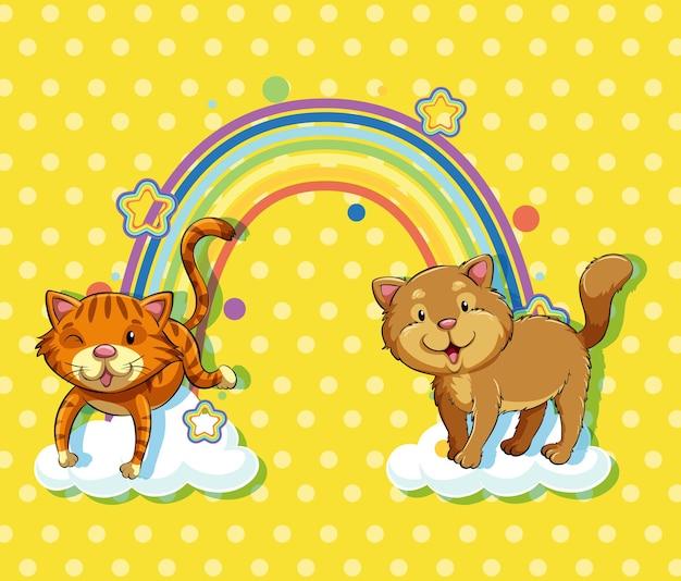 黄色の水玉模様の背景に虹と雲の上の2匹の猫
