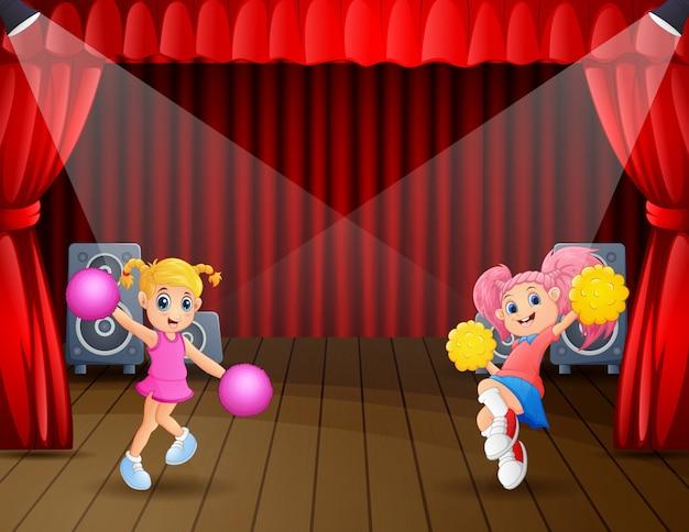 Two cheerleaders performing on stage