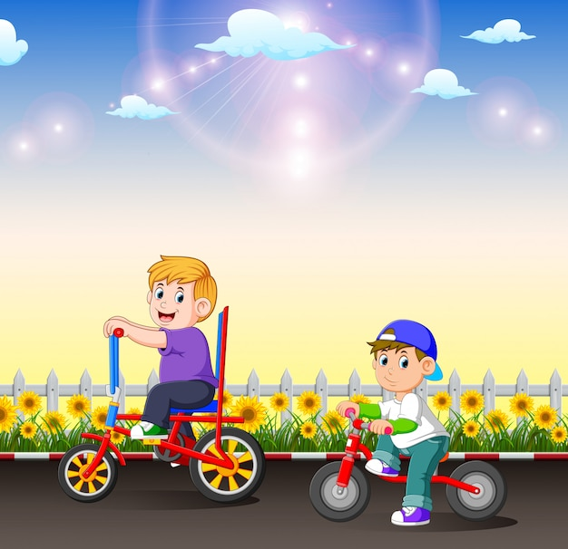 The two children are riding their bicycle in the afternoon
