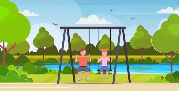 Ключевые слова на русском: два дети мальчик и худенькая девушка сидит на качели нездоровый образ жизни концепция ожирение дети качели вместе весело открытый летний парк пейзаж фон плоский полная длина горизонтальный