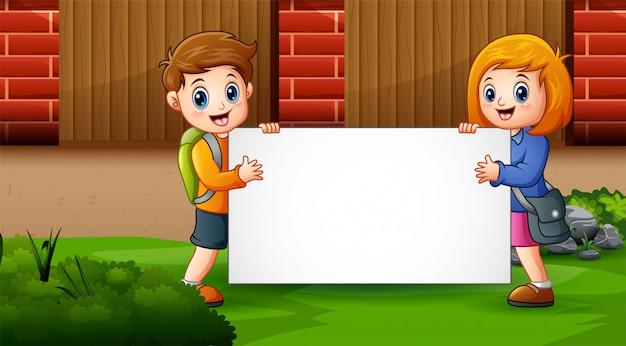Двое детей с пустым знаком на школьном дворе