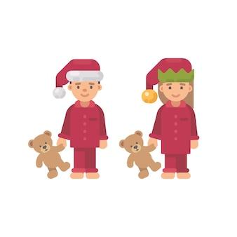 テディベアを保持しているクリスマスの帽子と赤いパジャマの2人の子供