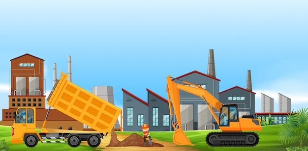 Два строительных грузовика работают на заводском поле