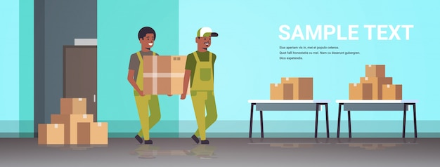 Two couriers in uniform carrying cardboard box package mail express delivery service concept   industrial factory workers working in stockroom of storehouse  full length horizontal