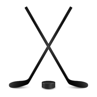 Two crossed hockey sticks and hockey puck. isolated on white backgrund.