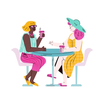 Two female friends sitting at table drinking take out coffee and talking