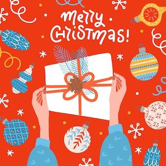 Две женские руки держат поверхность стола подарочной коробки с шарами и шарами, вид сверху поздравительной открытки bann ...