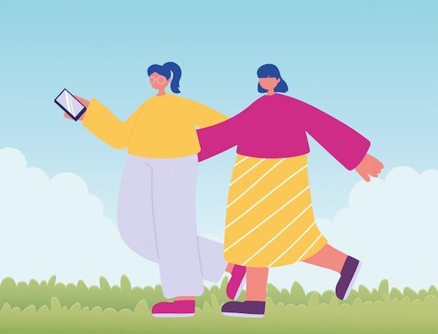 スマートフォンで歩いて2つのフレンドリーな女の子